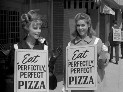 Endora and Samantha wear sandwich boards to advertise Perfect Pizza